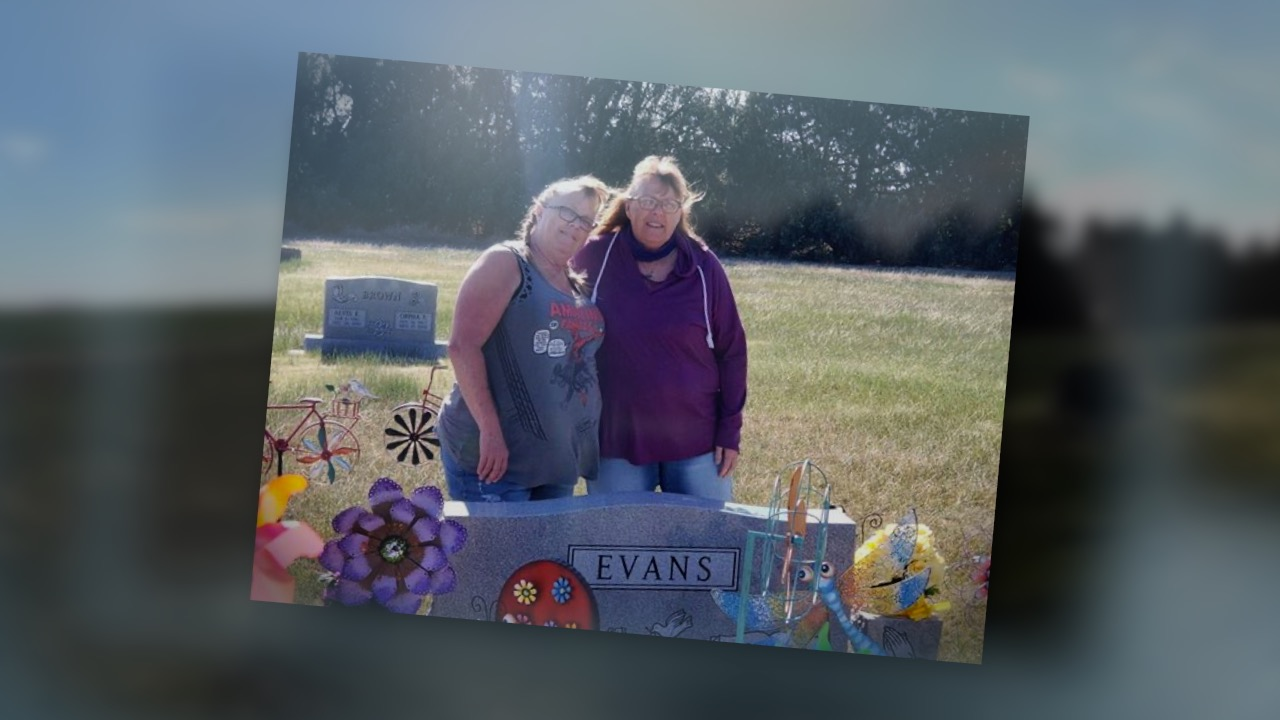 Tracy Dilka of Weld County and her sister Teresa visit their mother's grave in Kansas. Their mother, Marty Evans, died after contracting COVID-19.