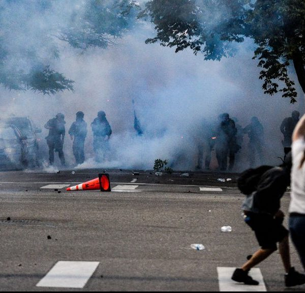 Police officers stand behind a wall of tear gas smoke after they attempt to disperse people marching along Colfax Ave. in Denver during the fourth consecutive day of protests in the aftermath of the death of George Floyd on May 31, 2020.