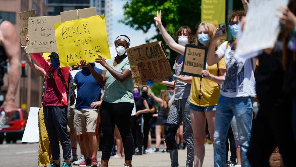 People hold signs near the Colorado State Capitol during the fifth consecutive day of demonstrations in the aftermath of the death of African American George Floyd on June 1, 2020 in Denver.