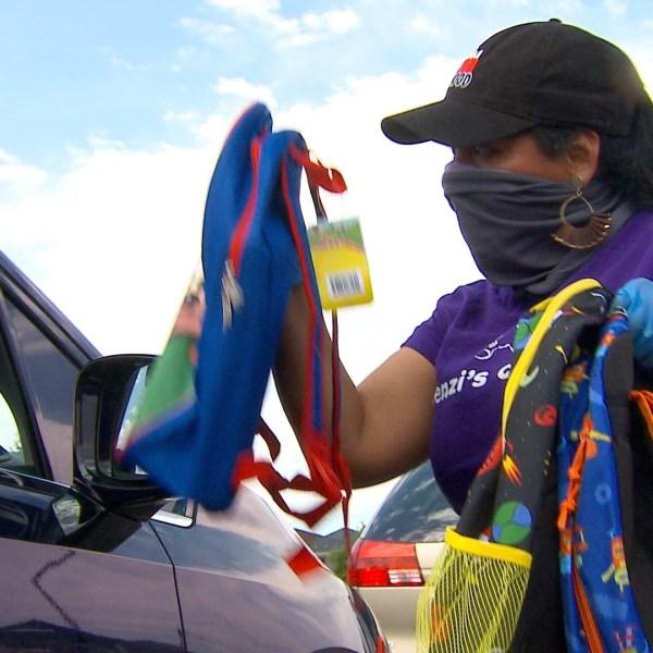 A volunteer hands out school supplies at a Packz 4 Kidz event on August 8, 2020.
