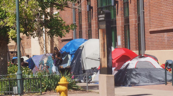 Tents along a city sidewalk during the day