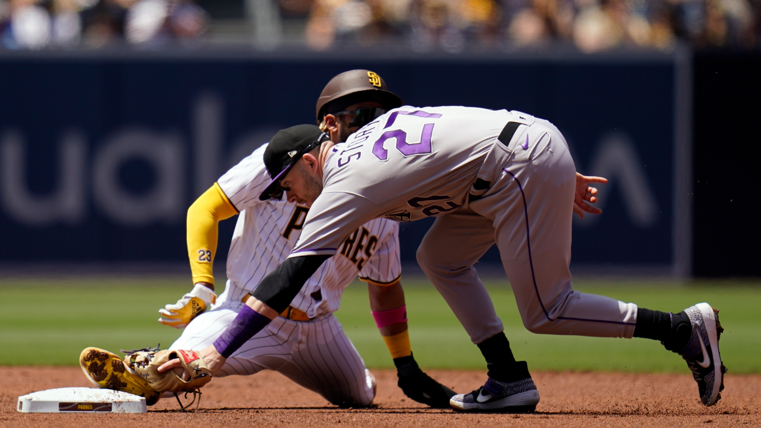 Colorado Rockies shortstop Trevor Story, front, reaches with his glove as San Diego Padres' Fernando Tatis Jr. safely steals second base