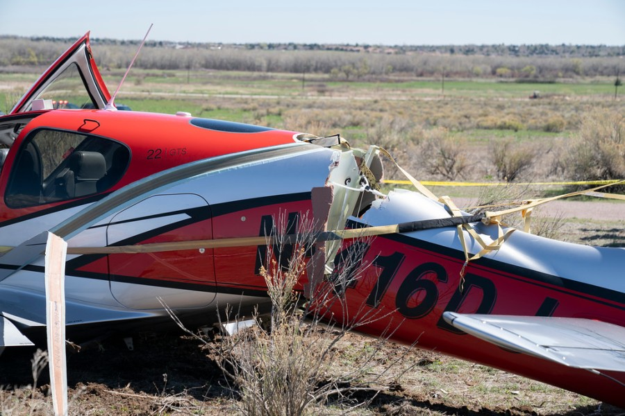 A small red and white airplane with a cracked fuselage and police tape surrounding it on a dry dirt field with blue sky on the horizon