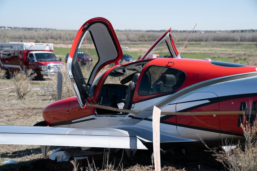 The side of a small red and white airplane with its two cockpit doors open and emergency vehicles in the background in a field with blue sky