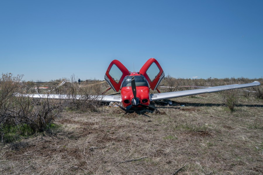 A small red and white airplane on dry dirt with its two doors lifted open on a field of dry dirt with blue sky