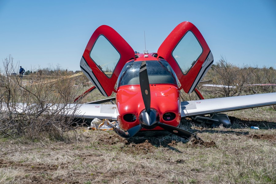 A close up of a small red and white airplane on dry dirt with its two doors lifted open on a field of dry dirt up of a small red and white airplane on dry dirt with its two doors lifted open on a field of dry dirt with blue sky