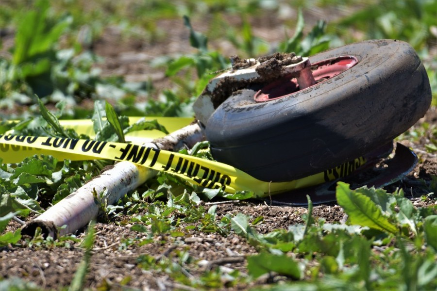 Closeup of police tape and a plane wheel on grass and dirt