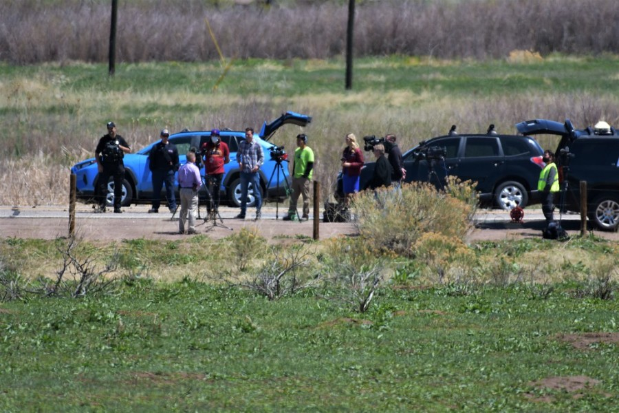 People lined up along the road with media cameras in front of two SUVs and surrounded by green grass fields