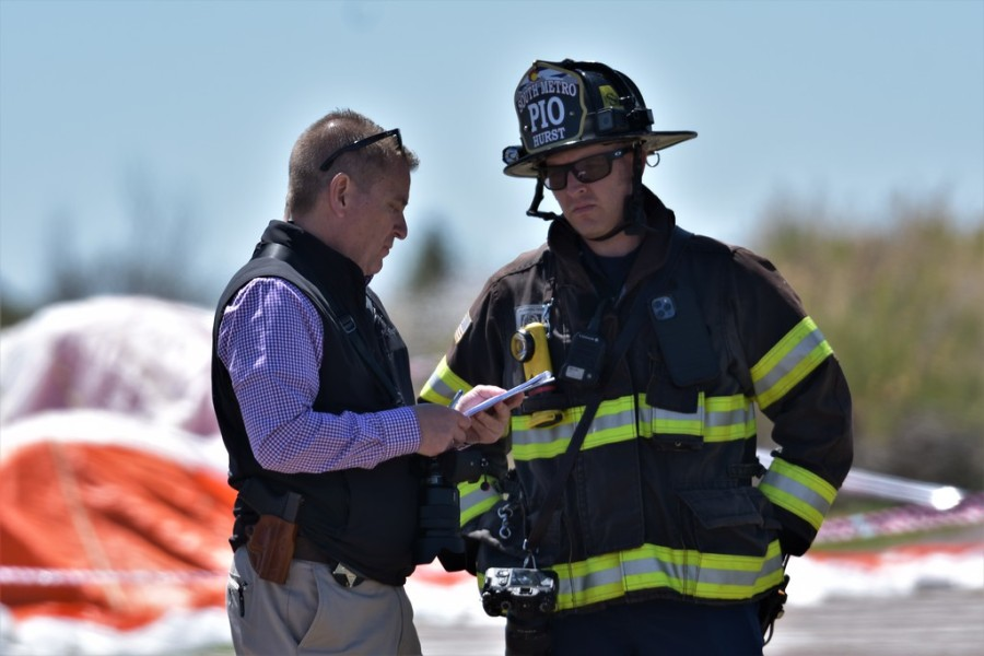 A closeup of a man in business attire talking to another man in firefighter attire with blue sky and the plane's parachute in the background