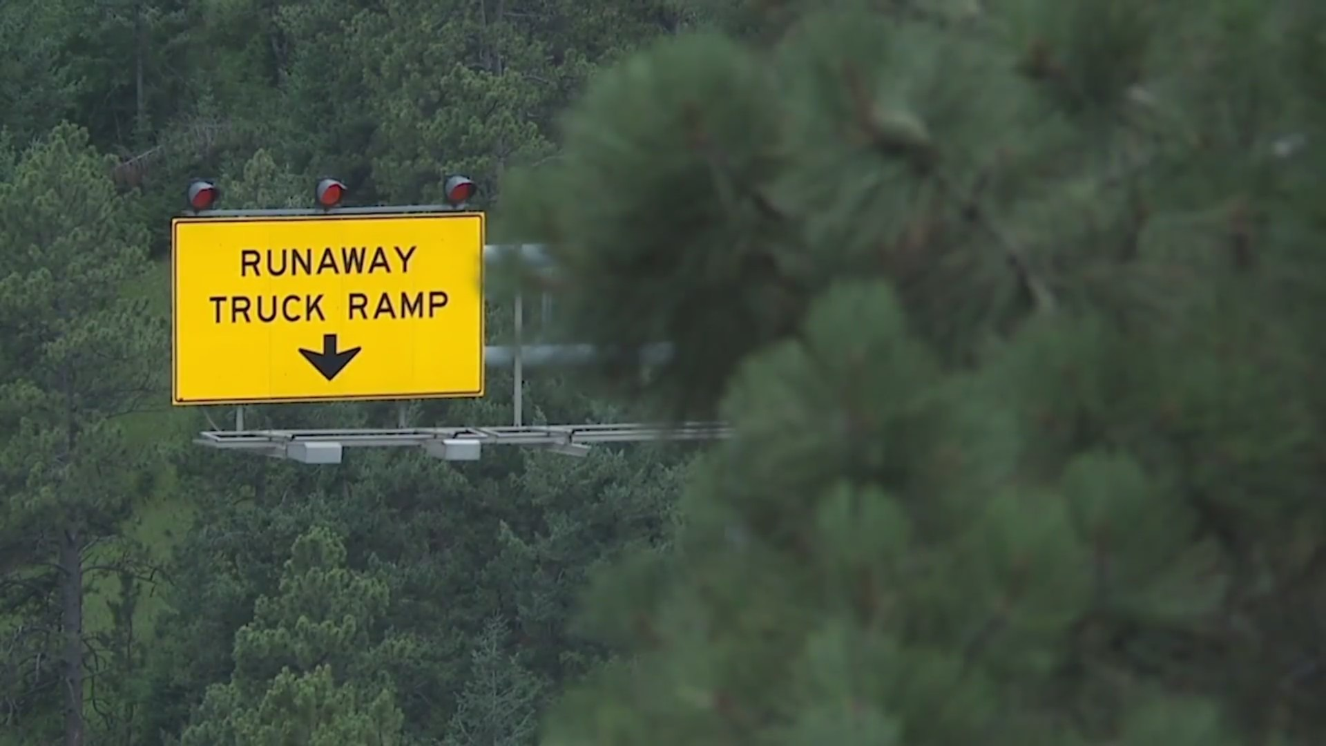 "A yellow road sign that says ""RUNAWAY TRUCK RAMP"" with an arrow pointing down"