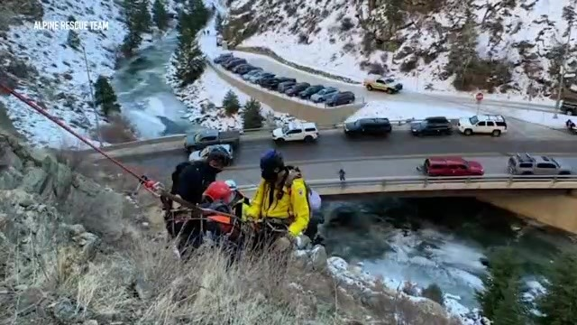 2 people carrying someone off a mountainside over a rushing creek near a parking lot