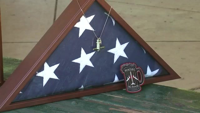 A U.S. flag folded and framed with tags hanging from it and a patch in front