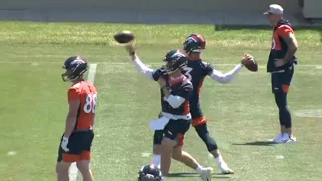 2 football players throwing footballs on a football field while in practice uniforms