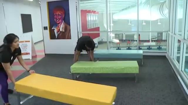 2 people moving benches inside a room overlooking an indoor pool