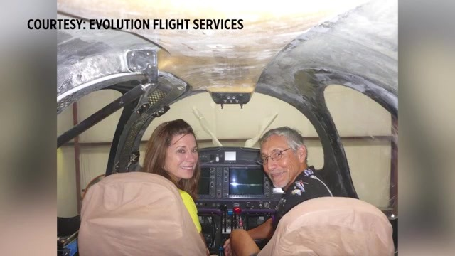 A woman and a man sit in an airplane cockpit
