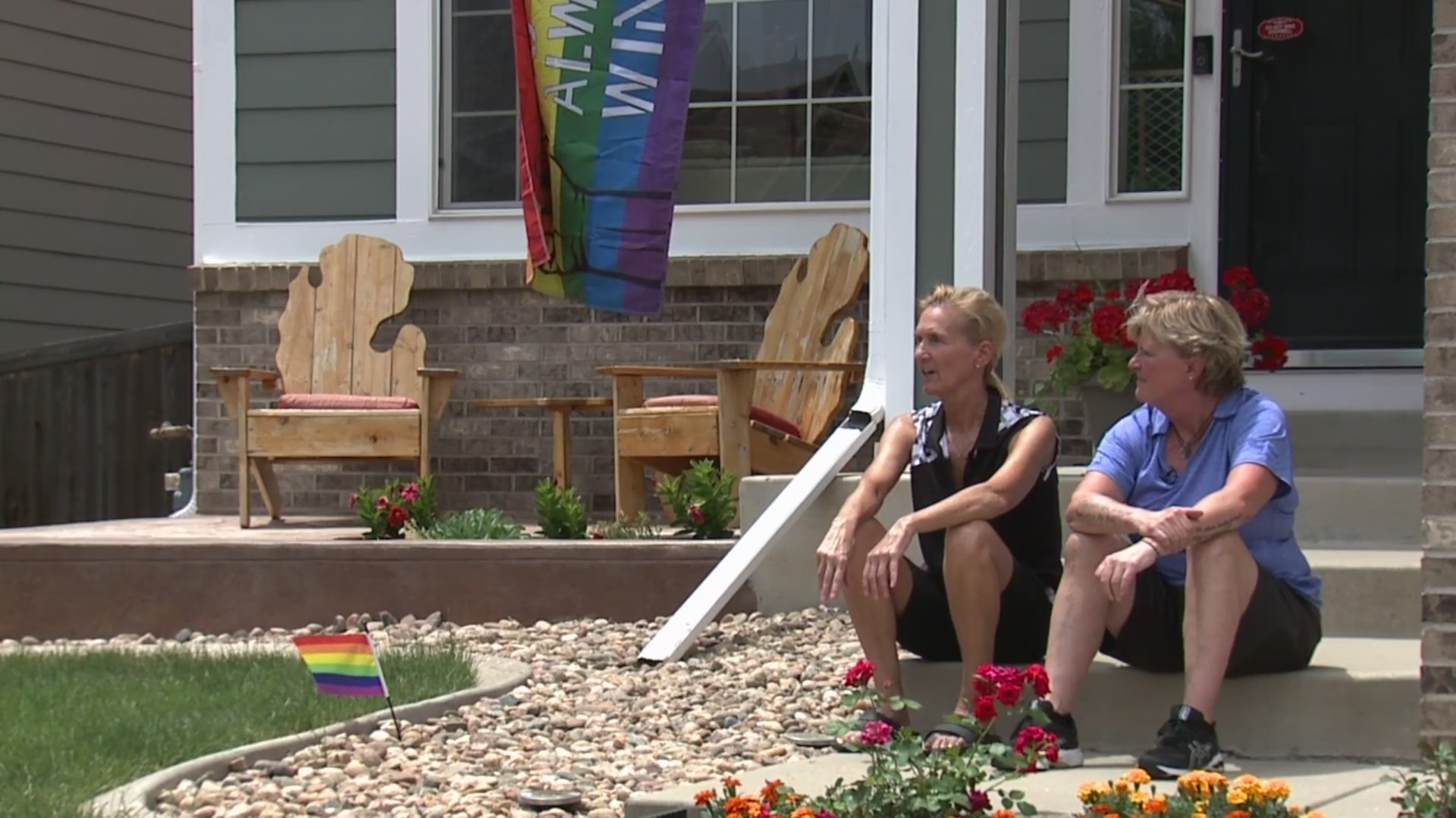 2 women sitting in front of their home with a rainbow flag nearby