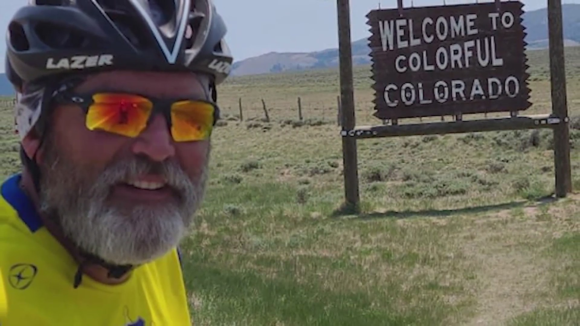 """A close-up of a man with sunglasses and a helmet and a white beard and mustache with a field in the background with a """"Welcome to Colorful Colorado"""" wooden sign and mountains in the distance"""