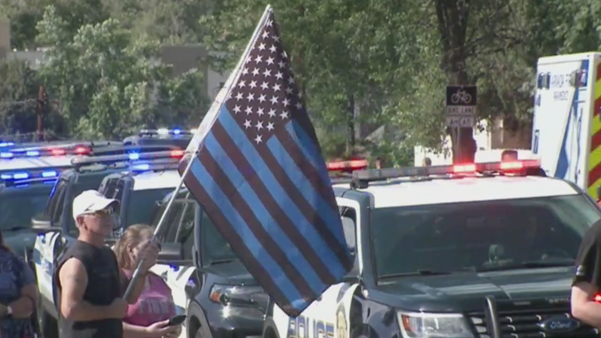 A man stands beside police vehicles with an American flag with the stripes colored blue and black