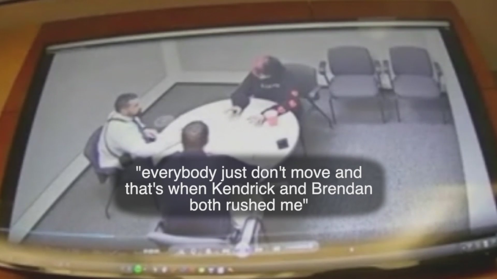 Surveillance vide of three people talking at a table