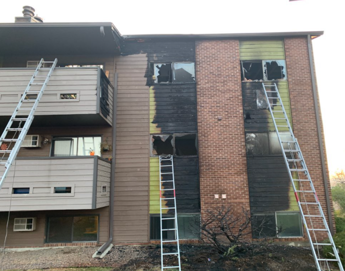 A two-story apartment building with charred flame damage on front siding and windows busted out