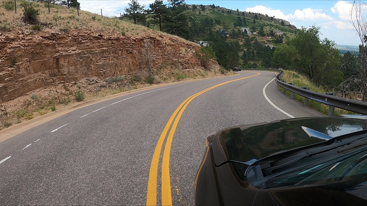 A paved road with double yellow center lines winds around the side of the foothills in daylight