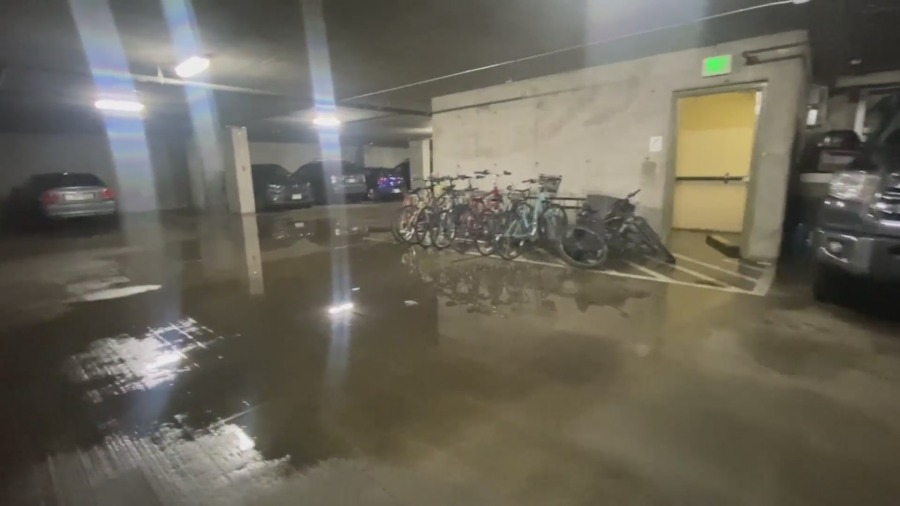 A flooded underground parking garage with bicycles and cars
