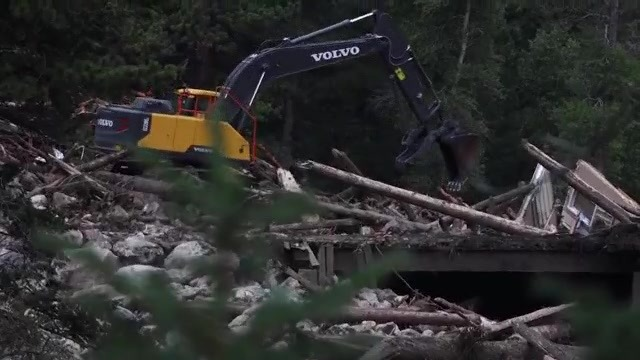 Heavy machinery removing knocked over trees and structure materials