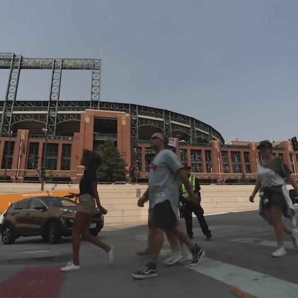 People in baseball jerseys walk across a crosswalk in front of Coors Field stadium